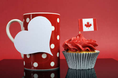 Red and white theme Canadian cupcake with maple leaf flag and red polka dot coffe mug with Happy Canada Day, Vive Le Canada, or copy space for your text here. photo