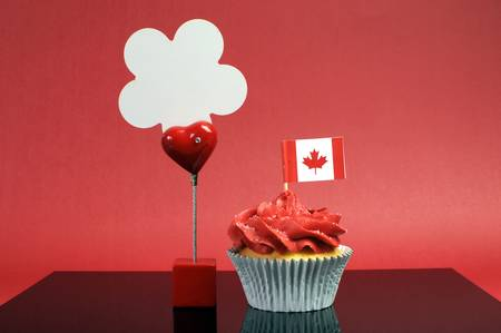 canada day: Red and white theme Canadian cupcake with maple leaf flag and sign with Happy Canada Day, Vive Le Canada, or copy space for your text here.