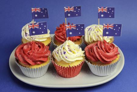 Australian theme red, white and blue cupcakes with national flag for Australia Day, Anzac Day or national holiday against a blue background. Close-up. Stock Photo - 19241266
