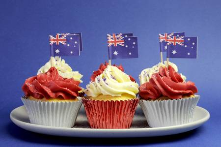 Australian theme red, white and blue cupcakes with national flag for Australia Day, Anzac Day or national holiday against a blue background. Stock Photo - 19241264