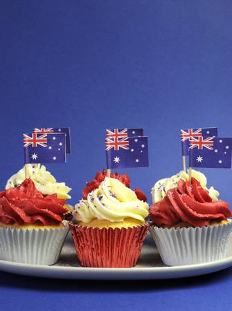 Australian theme red, white and blue cupcakes with national flag for Australia Day, Anzac Day or national holiday against a blue background. Vertical with copy space. photo