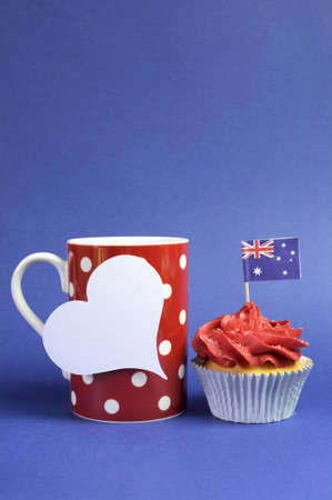 Australian theme red, white and blue cupcake with national flag and red polka dot coffee mug for Australia Day, Anzac Day or national holiday against a blue background. Vertical with copy space. Stock Photo - 19241263