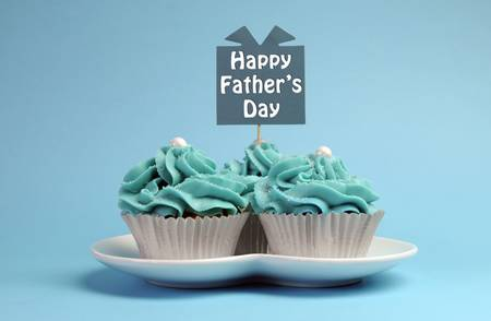Happy Fathers Day special treat blue and white beautiful decorated cupcakes with message on blue background  Stock Photo