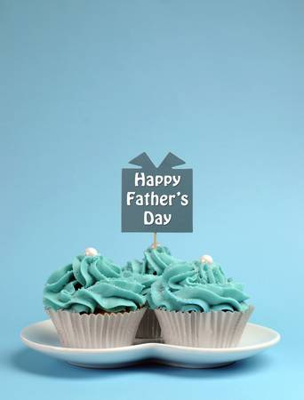 topper: Happy Fathers Day special treat blue and white beautiful decorated cupcakes with message on blue background  Vertical with copy space for your text here  Stock Photo