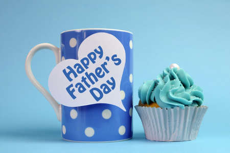 Happy Fathers Day special treat blue and white beautiful decorated cupcakes with message on blue background, with blue polka dot coffee mug  Stock Photo - 19331051