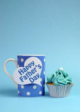 Happy Fathers Day special treat blue and white beautiful decorated cupcakes with message on blue background, with blue polka dot coffee mug  Vertical with copy space for your text here