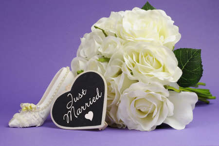 Wedding bouquet of white roses with good luck high heel shoe and heart sign with Just Married message, against purple lilac background  photo
