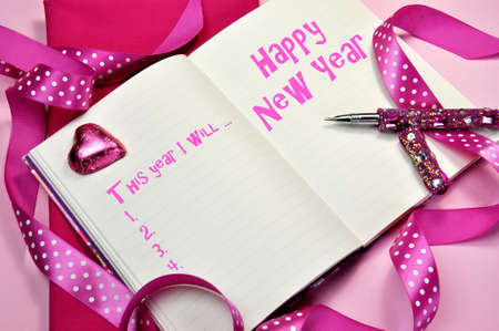 Happy New Year resolutions in diary jounrnal book with pretty feminine pink ribbons, heart chocolate and pen