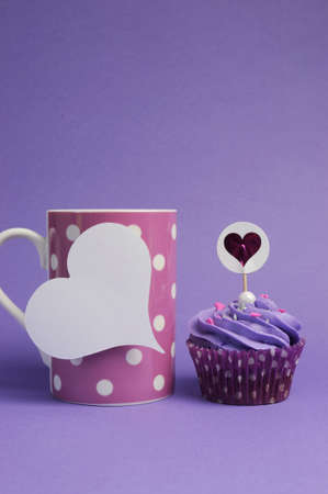 Mauve purple decorated cupcakes for children or teens birthday, or bachelorette, bridal or baby shower party function, with pink polka dot coffee mug and heart gift tag with copy space for your text here