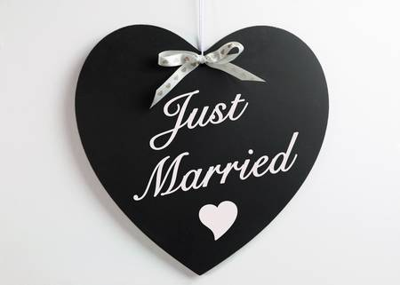 honeymoons: Heart shape blackboard with white hearts ribbon against a white background with Just Married message for weddings or honeymoons