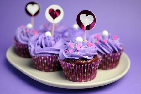 supper: Mauve purple decorated cupcakes for children or teens birthday, or bachelorette, bridal or baby shower party function  Closeup with bokeh  Stock Photo