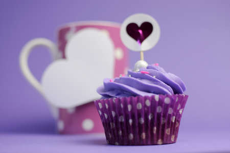 Mauve purple decorated cupcakes for children or teens birthday, or bachelorette, bridal or baby shower party function, with pink polka dot coffee mug and heart gift tag with copy space for your text here  photo