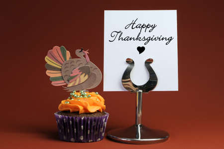 Happy Thanksgiving message on table stand with orange cupcake with turkey decoration. photo