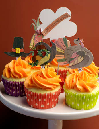Happy Thanksgiving decorated cupcakes with turkey, pilgrim hat and corn toppers on cake stand against a brown background.