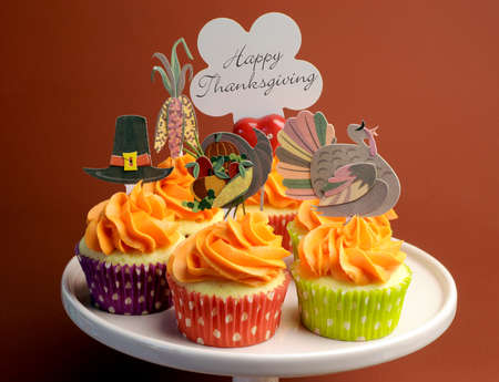happy feast: Happy Thanksgiving decorated cupcakes with turkey, pilgrim hat and corn toppers on cake stand against a brown background, with Happy Thanksgiving message.
