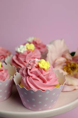 topper: Beautiful pink decorated cupcakes on pink cake stand for birthday, wedding or female special event occasion. Vertical close up with bokeh.