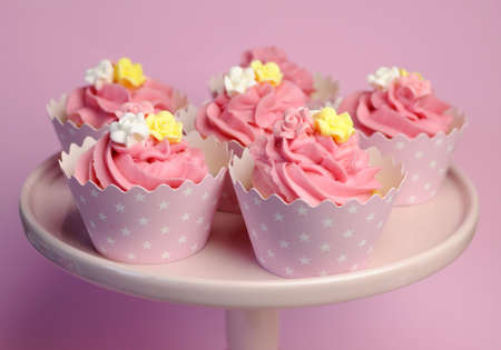 topper: Beautiful pink decorated cupcakes on pink cake stand for birthday, wedding or female special event occasion, with pink, yellow and white fondant roses and pink star cups.