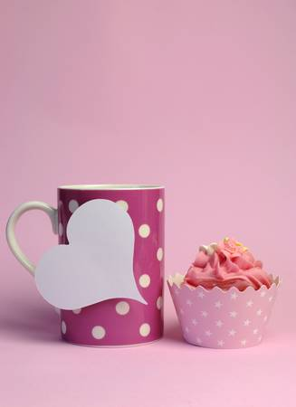 topper: Pink polka dot coffee mug with pink cupcake and blank white heart shape gift tag for your text here, for female birthday, mothers day, or special occasion event. Vertical with copy space.