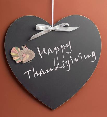 Happy Thanksgiving message written on heart shape blackboard with turkey motif decoration. photo