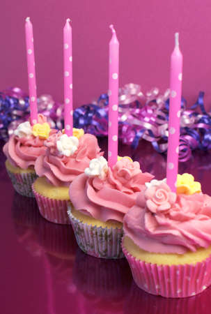 Pink brithday cupcakes with polka dot candles against a pink background. Vertical with shallow focus on second cupcake. photo