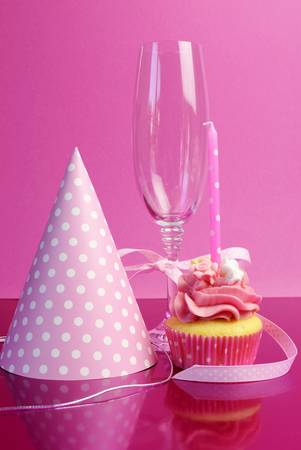 Pink brithday cupcake with polka dot candles against a pink background, with party hat and champagne glass with pink polka dot ribbon. photo