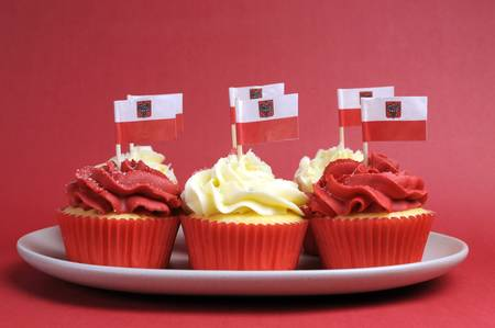 independance: Polish red and white decorated cupcakes with Poland flags for November 11, National Independence Day celebrations or national holiday party.