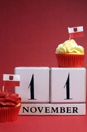 Calendar date for Poland National Independence Day, Novemebr 11, with mini cup cakes and Polish flags in red and white theme colors. Vertical with copy space. photo