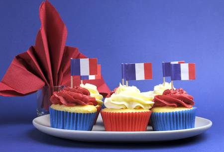 fourteenth: French theme red, white and blue mini cupcake cakes with flags of France and fleur-de-lis red napkin for National holidays of France, Bastille Day, the Fourteenth of July.