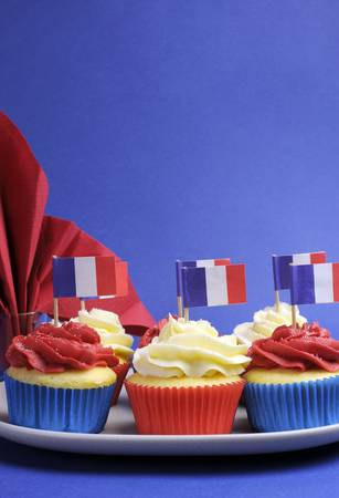 French theme red, white and blue mini cupcake cakes with flags of France and fleur-de-lis red napkin for National holidays of France, Bastille Day, the Fourteenth of July. Vertical with copy space for your text here. Stock Photo - 20297287