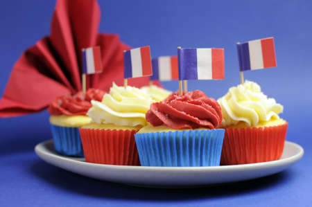shallow dof: French theme red, white and blue mini cupcake cakes with flags of France and fleur-de-lis red napkin for National holidays of France, Bastille Day, the Fourteenth of July. Close up with shallow DOF bokeh. Stock Photo