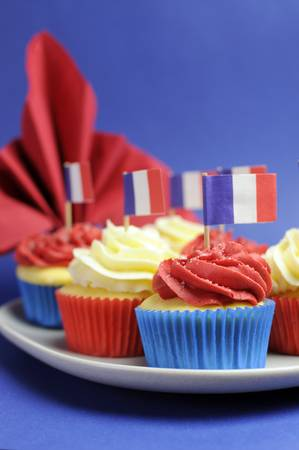 French theme red, white and blue mini cupcake cakes with flags of France and fleur-de-lis red napkin for National holidays of France, Bastille Day, the Fourteenth of July. Close up vertical. photo