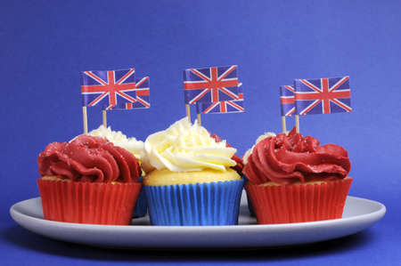 English theme red, white and blue cupcakes with Great Britain Union Jack flags for national party celebrations. photo