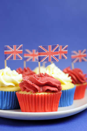 English theme red, white and blue cupcakes with Great Britain Union Jack flags for national party celebrations. Close up vertical. photo