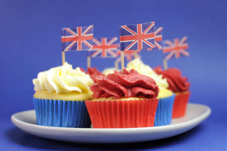 british food: English theme red, white and blue cupcakes with Great Britain Union Jack flags for national party celebrations. Close up with shallow DOF bokeh.