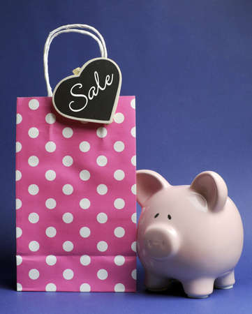 Retail Shopping Sale promotion with pink polka dot bag and piggy bank with Sale message on heart shape blackboard tag on blue background. photo