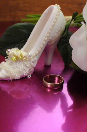 Wedding bridaal bouquet of white roses on pink background with good luck shoe and wedding ring. Vertical with copy space. photo