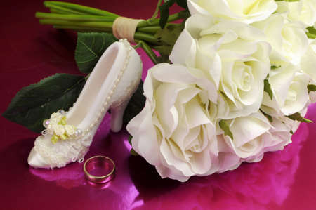 Wedding bridaal bouquet of white roses on pink background with good luck shoe and wedding ring. photo