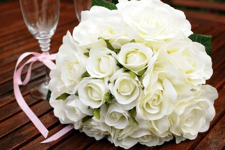 Wedding bridaal bouquet of white roses with two champagne glasses with pink polka dot ribbon on outdoor garden table setting after rain. Close up.