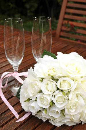 reception desk: Wedding bridaal bouquet of white roses with two champagne glasses with pink polka dot ribbon on outdoor garden table setting after rain. Vertical.