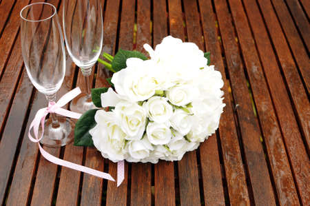 Wedding bridaal bouquet of white roses with two champagne glasses with pink polka dot ribbon on outdoor garden table setting after rain. Horizontal with copy space. photo