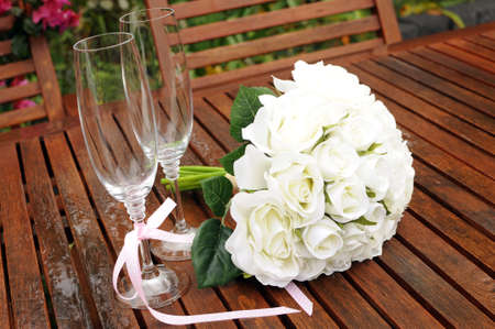 Wedding bridaal bouquet of white roses with two champagne glasses with pink polka dot ribbon on outdoor garden table setting after rain. photo