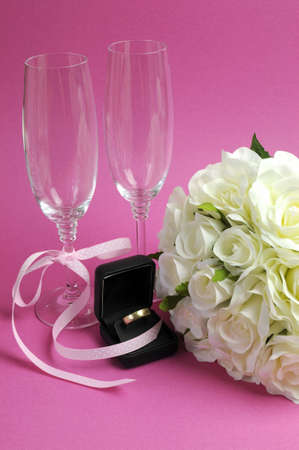 Wedding bridal bouquet of white roses on pink background with pair of champagne flute glasses and wold weggind ring in black jewellery box. Vertical. photo