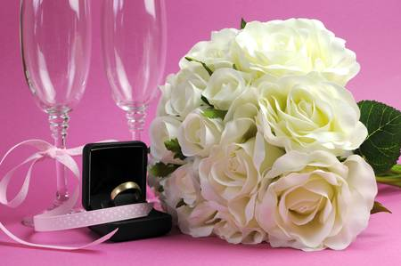 Wedding bridal bouquet of white roses on pink background with pair of champagne flute glasses and wold weggind ring in black jewellery box. photo
