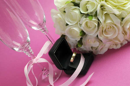marriage invitation: Wedding bridal bouquet of white roses on pink background with pair of champagne flute glasses and wold weggind ring in black jewellery box.