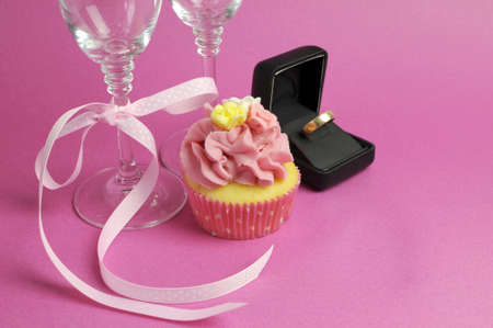 Wedding theme bridal pair of champagne flute glasses with pink cupcake and wedding ring in black jewlery box against a pink background. photo