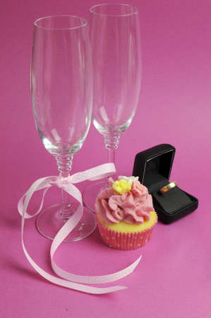 Wedding theme bridal pair of champagne flute glasses with pink cupcake and wedding ring in black jewlery box against a pink background. Vertical. photo