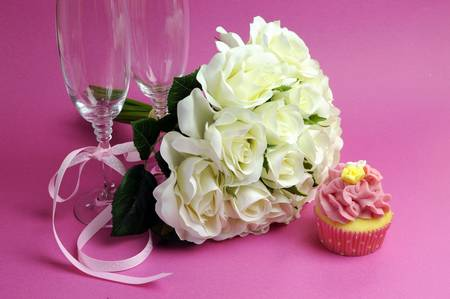 Wedding bridal bouquet of white roses on pink background with pink cupcake and pair of two champagne flute glasses. photo