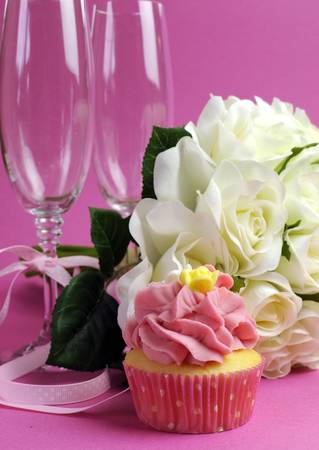 wedding cake: Wedding bridal bouquet of white roses on pink background with pink cupcake and pair of two champagne flute glasses. Vertical. Stock Photo