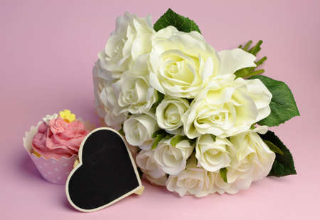 Wedding white roses bouquet with pink cupcake with heart shape blackboard with copy space for your text here. photo