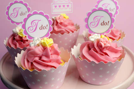small cake: Pink wedding cupcakes with I Do topper signs on pink cake stand - close up.